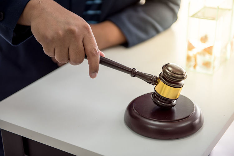 Close-up of lawyer hand holding gavel at desk in courtroom