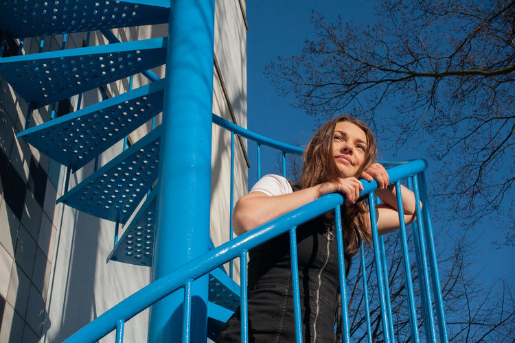 Low angle view of woman on railing against blue sky
