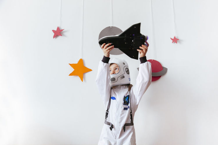 Girl wearing space suit playing with rocket against wall at home