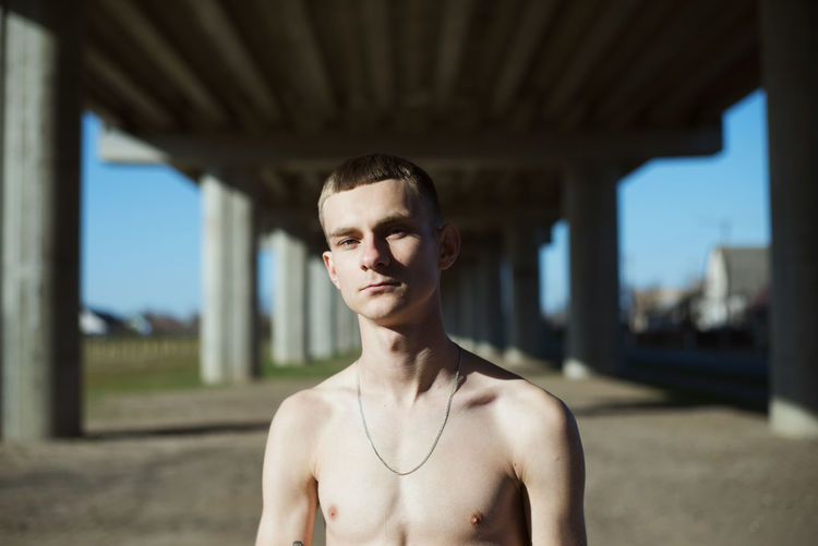 Portrait of shirtless young man outdoors