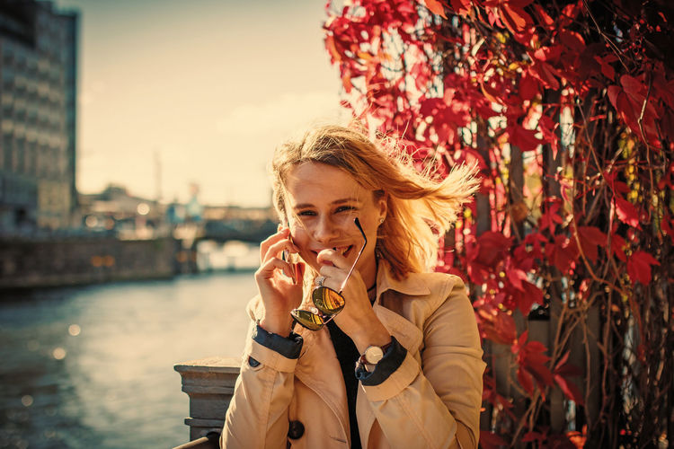 Portrait Of Cheerful Young Woman Talking On Phone By River
