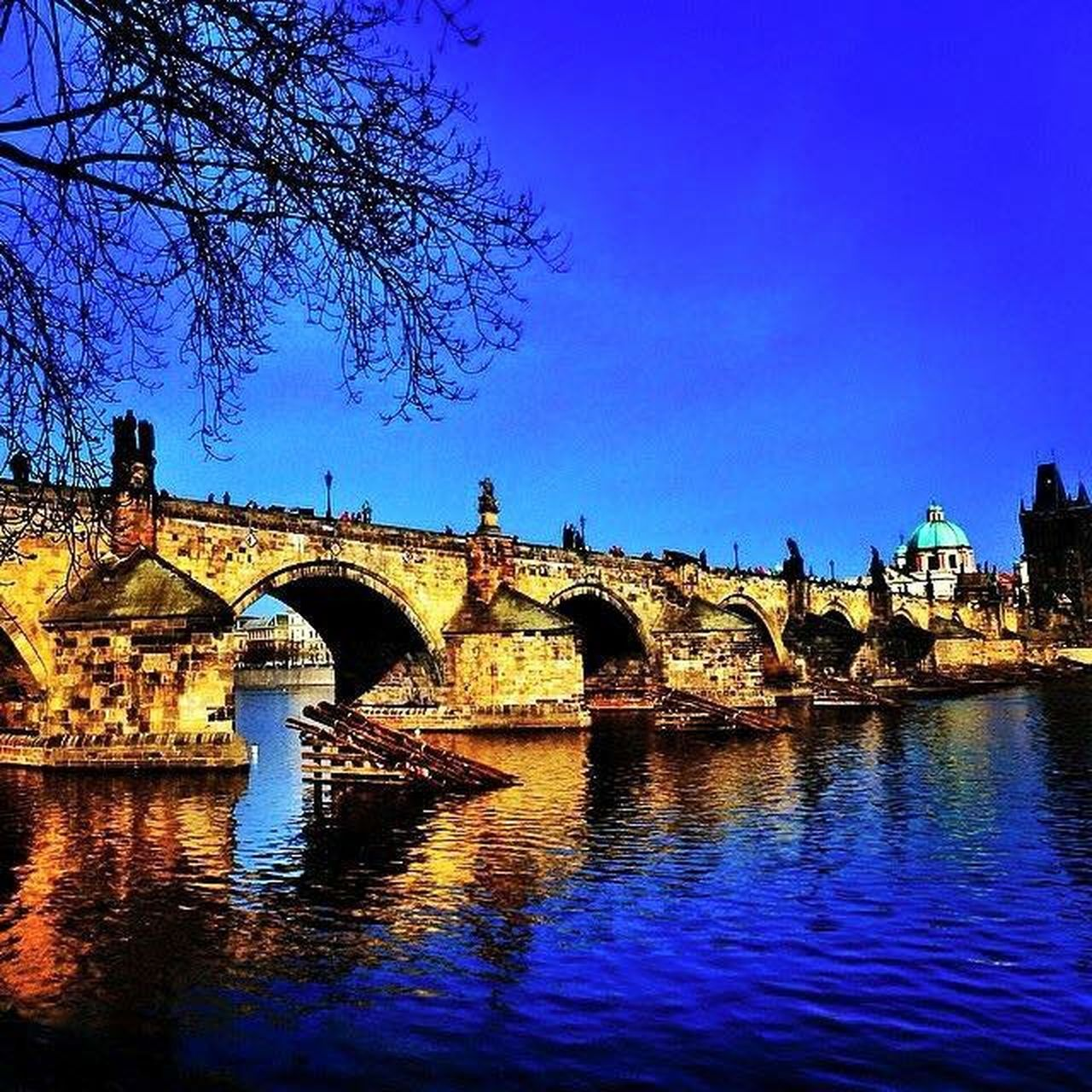 arch, architecture, built structure, water, bridge - man made structure, history, connection, reflection, travel destinations, day, blue, no people, outdoors, building exterior, sky, clear sky, tree, city, ancient civilization