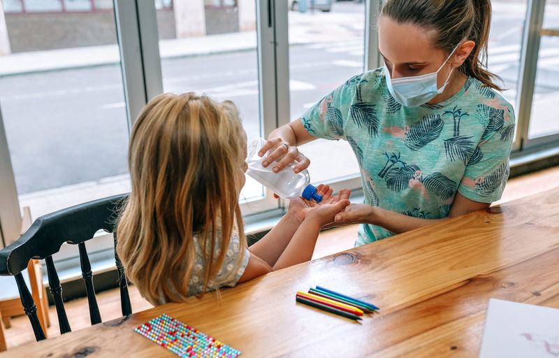 Woman and daughter using sanitizer sitting on table
