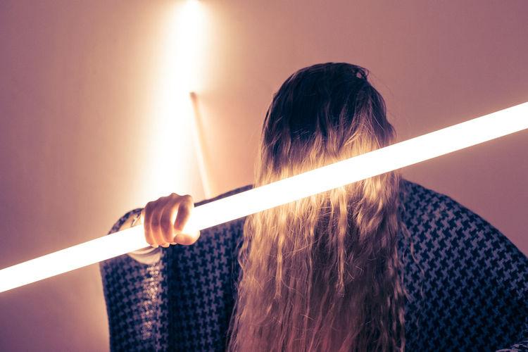 Woman holding illuminated fluorescent light against wall