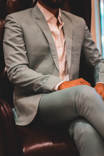 Midsection Indoors  Men Real People Clothing Front View Occupation Business Person Formalwear People Adult Business Necktie Well-dressed Menswear Businessman Males  Holding Suit Sitting Exploring Fun Springtime Decadence The Portraitist - 2019 EyeEm Awards The Architect - 2019 EyeEm Awards
