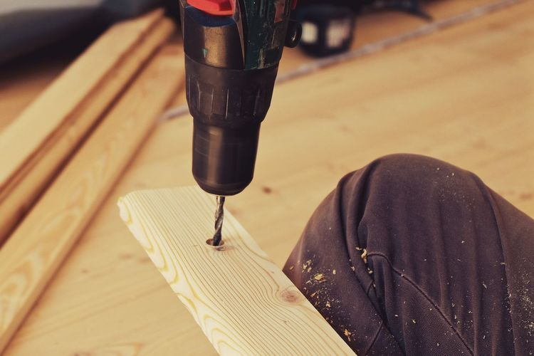 Cropped image of man using power tool on plank