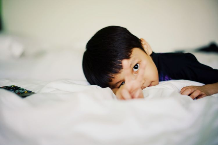 Bed Furniture Lying Down Child Childhood Portrait Indoors  Headshot One Person Black Hair Relaxation Selective Focus Bedroom Innocence Domestic Room Real People Cute Looking At Camera 2018 In One Photograph My Best Photo The Portraitist - 2019 EyeEm Awards