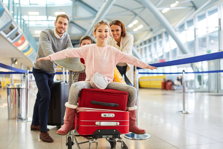 Portrait of happy family pushing girl sitting on luggage cart at airport