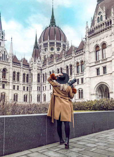 Rear view of woman standing against hungarian parliament building