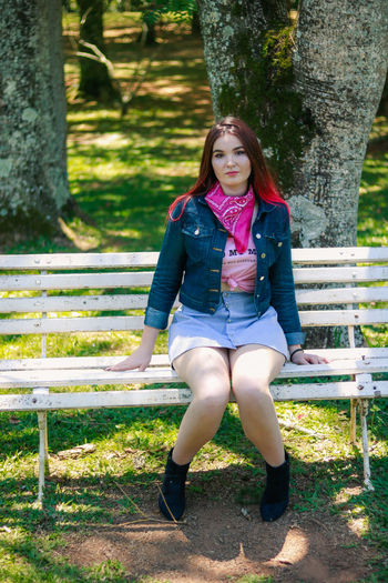 Smiling young woman sitting on bench in park