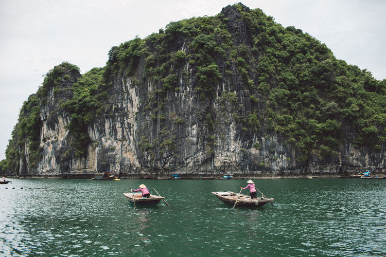 People Rowing Boat On Halong Bay By Mountains