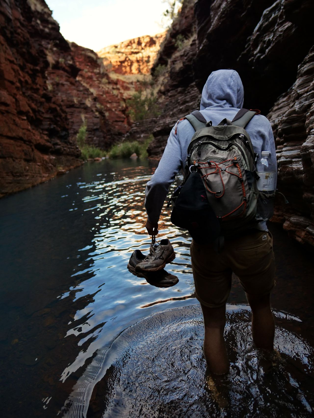 Rear view of young man with backpack standing in river amidst mountains