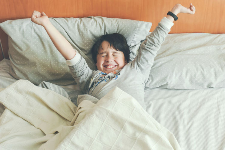Bed Bedroom Relaxation Happiness Emotion Childhood Smiling Child Human Limb Eyes Closed  Human Arm Happiness Wake Up! Morning Bed Bedtime Energy Lifestyle Up Laziness Sleeping Sleep Sleepyhead Happy Smile Stretch Stretching Pillow Blanket Awake Portrait Hands Resting Lying Pajamas People Healthy Lifestyle Home Cute Rest Kid