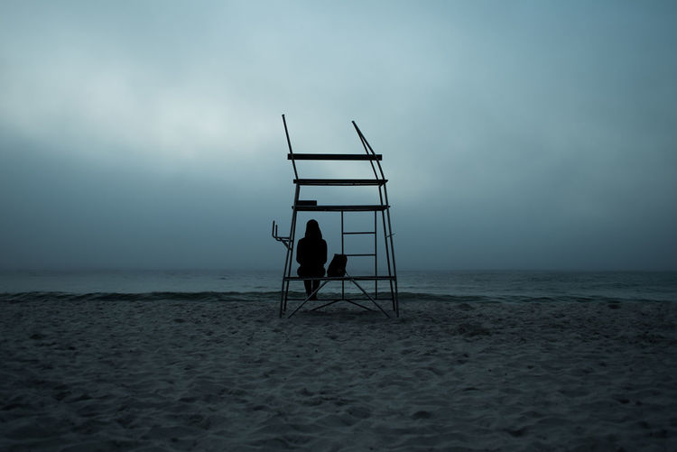 Silhouette woman sitting on lifeguard chair at beach against sky
