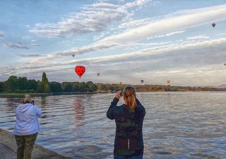 Men standing on hot air balloon against sky