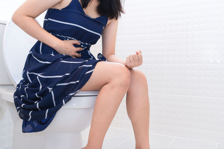 Midsection of woman suffering from constipation while sitting on toilet bowl in bathroom