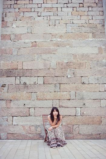 Full length of woman sitting on brick wall
