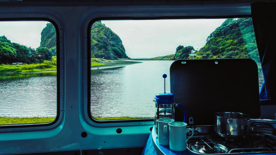 coffee time in camper with a view in new zealand Camping Coffee Aboutpassion Beauty In Nature Camper Day Glass - Material Mode Of Transportation Mountain Nature Nautical Vessel No People Outdoors Plant River Scenics - Nature Transparent Transportation Travel Tree Vanlife Vehicle Interior Water Window