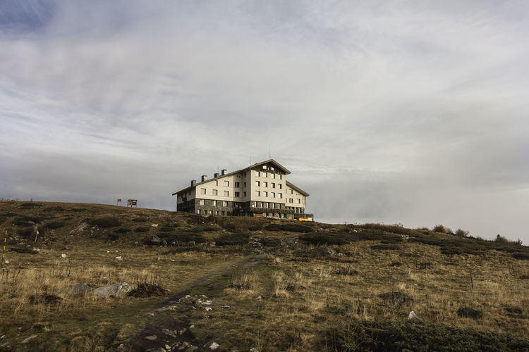 A hotel in the early morning Hiking Winter Architecture Building Building Exterior Built Structure Cloud - Sky Clouds Day Field History Hotel Land Landscape Lodge Mountains Nature No People Ominous Outdoors Sky