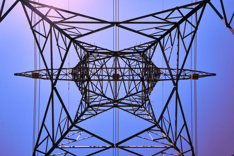 Directly below shot of of electricity pylon against clear sky