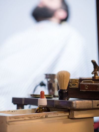 Close up of bottle and shaving brush on table