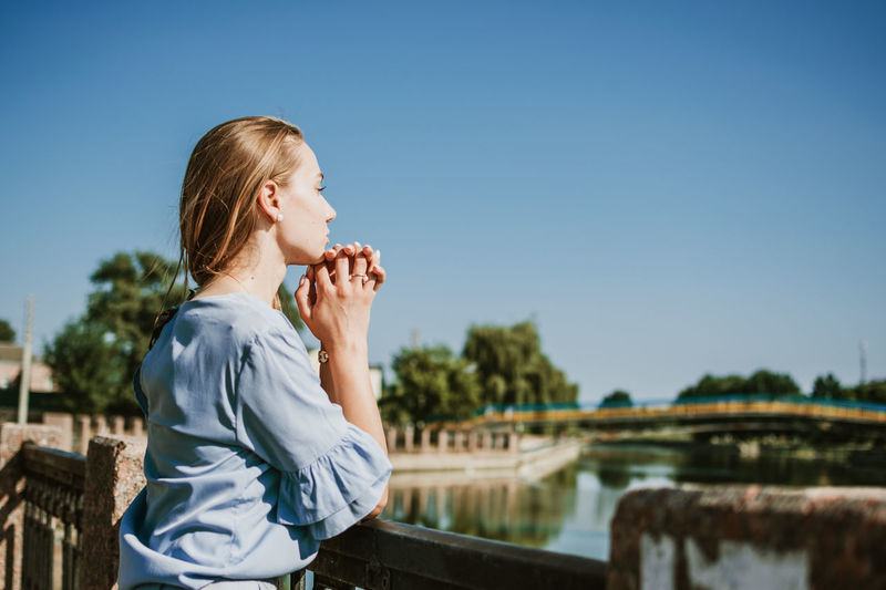 Lonely pensive young blonde woman in blue dress standing near the city river in summer sun day