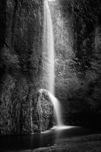Waterfall from above on the rock, made up of dark basalt banks, forming