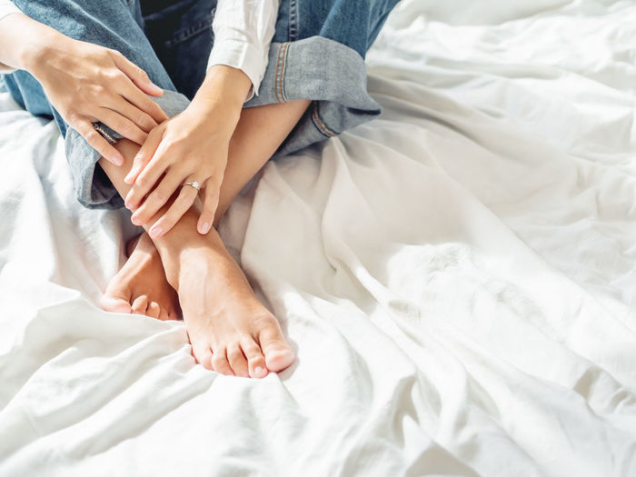 Woman with engagement ring on finger sits on unmade bed. female in classic blue jeans.