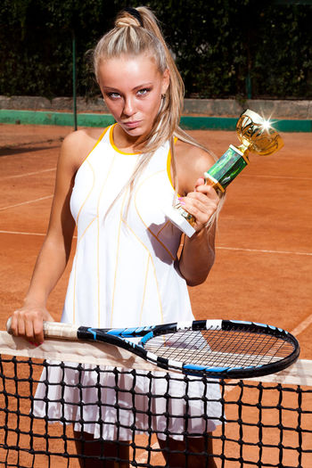 Woman in a white tennis dress holding the winning trophy in her hand One Person Real People Blond Hair Front View Women Lifestyles Leisure Activity Hair Holding Day Music Young Adult Container Standing Casual Clothing Three Quarter Length Drink Young Women Tennis Racket Beautiful Woman