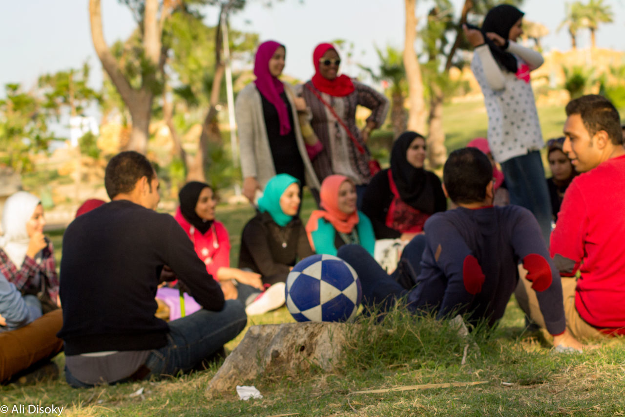 soccer, real people, sitting, lifestyles, soccer player, large group of people, men, sport, leisure activity, focus on foreground, outdoors, soccer ball, day, soccer uniform, grass, togetherness, soccer field, sports uniform, tree, sports team, sportsman, people