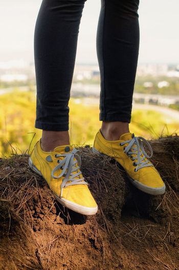 Standing at the edge of the city. At The Edge Casual Edge Paint The Town Yellow Sport Shoes Standing At The Edge Balance Balancing Border Edge Of The Town Edging Low Section Shoelaces Sportshoes Standing The End White Shoelaces Yellow Yellow Shoes