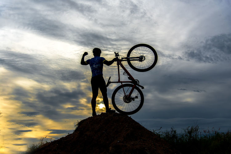 Low angle view of man with bicycle against cloudy sky