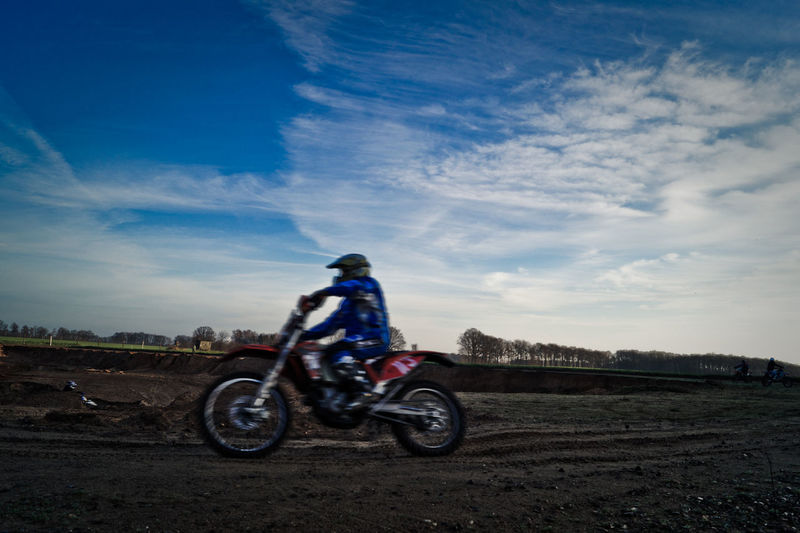 Motocross racer on dirt road against sky