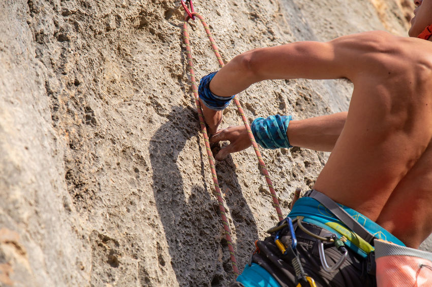 Close up hands of young man climber in a crack while climbing a wall on a sunny day. Close-up Hand Climbing Holding Powder Handhold Rock Climber Young Adult Mountain Hanging Cliff Strong Man Fingers Outdoors Extreme Sports Sport Grip Magnesium Athlete RISK Challenge Rope Caucasian