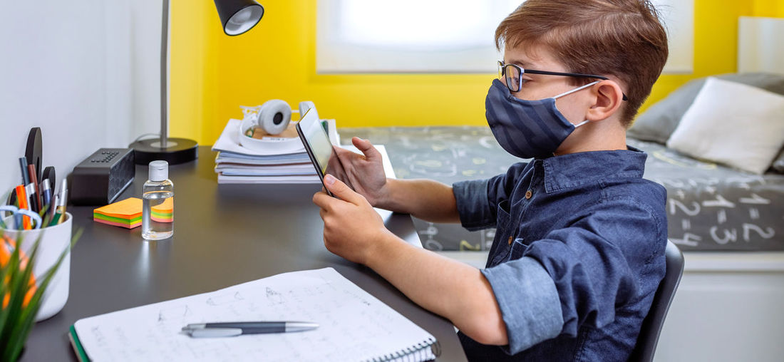 Rear view of boy using mobile phone while sitting on table
