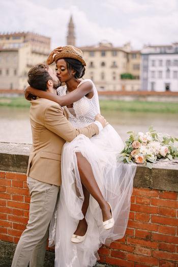 Bridegroom kissing by wall against buildings