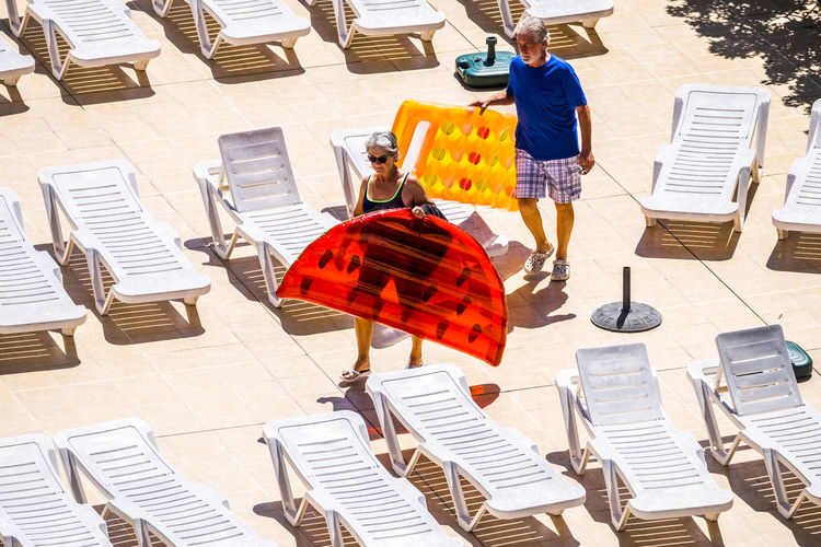 High angle view of senior couple holding inflatables walking by lounge chairs