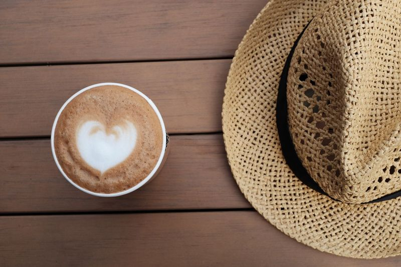 Directly Above Shot Of Coffee With Hat On Table