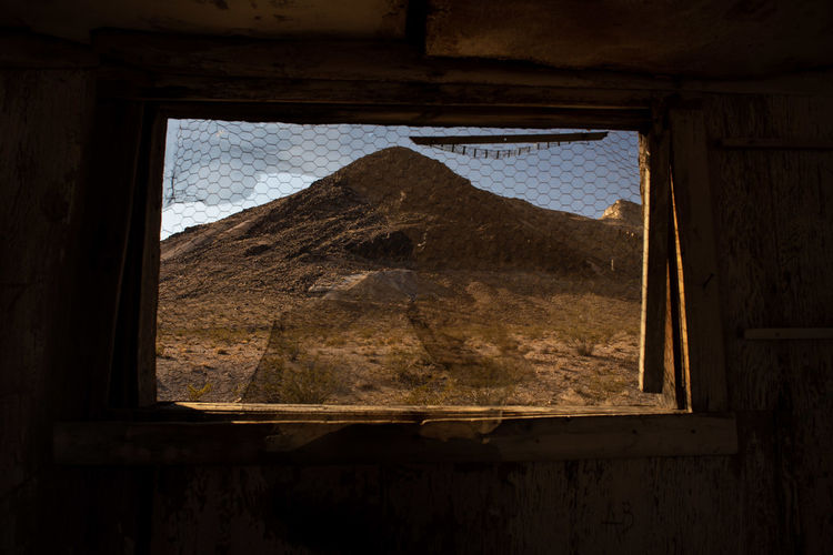 View of hill in desert landscape thru abandoned building window of ghost town