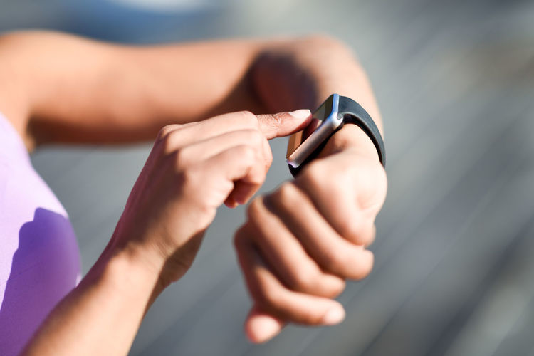 Woman using smartwatch touching touchscreen in active sports activity. Close-up of hands and wrist with smart watch screen. Exercising Woman Close-up Device Fitness Girl Healthy Lifestyle Human Body Part Human Hand Lifestyles One Person Outdoors Real People Runner Smart Watch Smartwatch Sport Sports Clothing Technology Watch Workout Young Adult