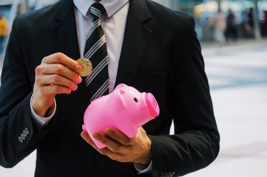 midsection smart business man in black suit holding piggy bank, golden Bitcoin on city background, digital technology, virtual currency, financial, investment, saving money, payment online concept City Electronic Gold Growth Man Pink Wallet Bitcoin Business Cash Coin Currency Digital Expenses Finance Future Holding Income Investment Midsection Piggy Bank Savings Successful Technology Wealth