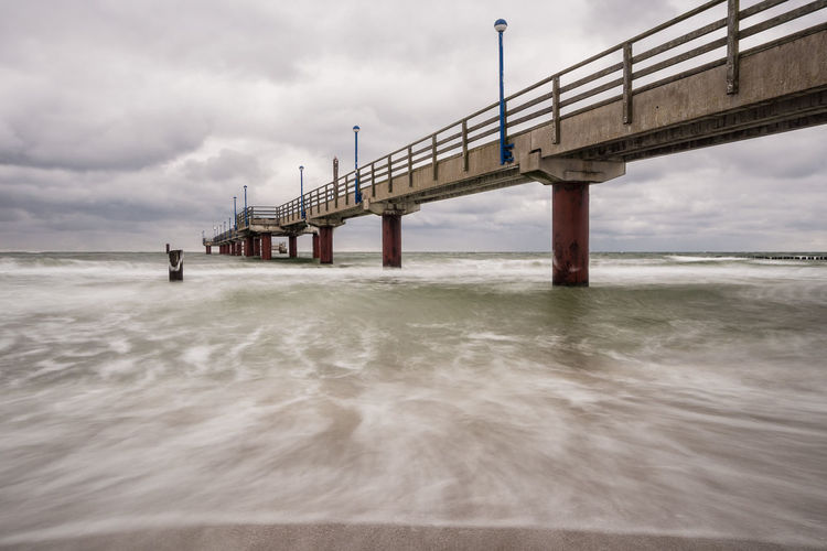 Low angle view of bridge on sea against cloudy sky