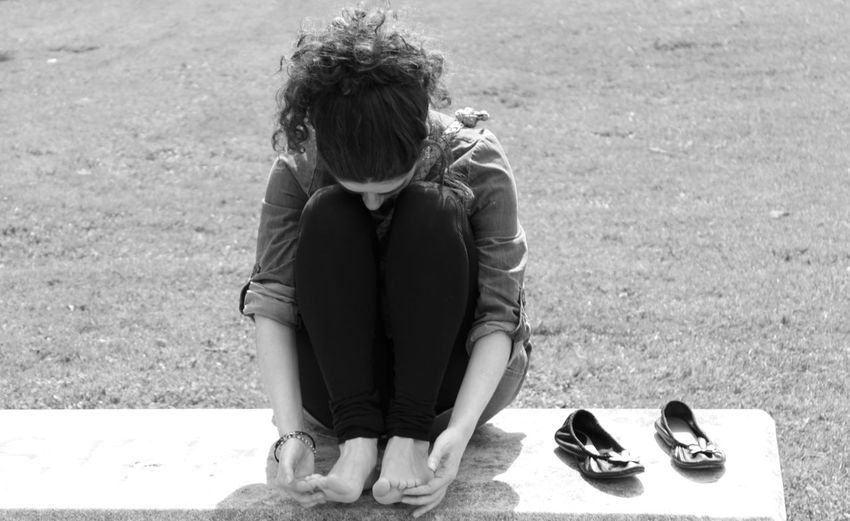 Woman Touching Her Feet While Sitting On Exercise Mat At Park