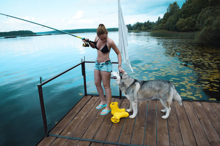 Full length of woman with husky dog fishing
