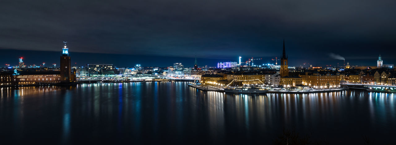 Illuminated buildings in stockholm city at night with reflections in waterfront