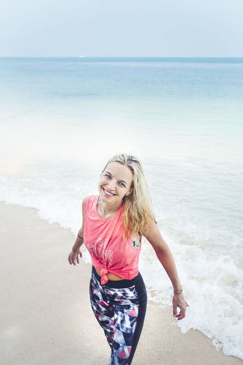 Caucasian woman is happy at the beach Beach Beautiful Woman Beauty In Nature Blond Hair Day Front View Happiness Horizon Over Water Leisure Activity Lifestyles Looking At Camera Nature One Person Outdoors Portrait Real People Sand Sea Shore Smiling Vacations Water Wave Young Adult Young Women