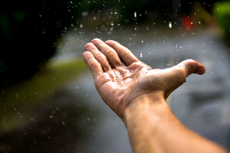 Cropped hand of man holding raindrops