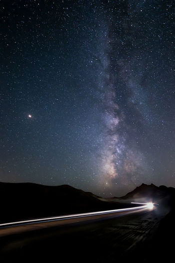 Light trails on road against star field at night