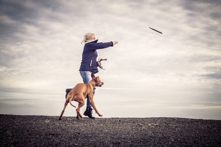 Woman With Dog At Field Against Cloudy Sky