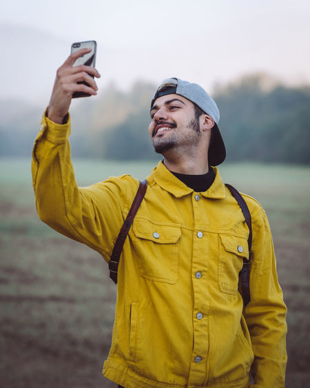 Man using mobile phone standing outdoors